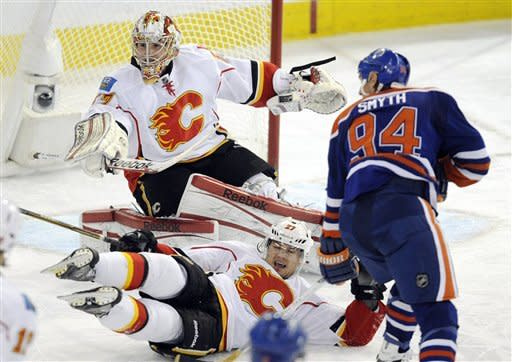 Calgary Flames' Derek Smith, center, falls while defending goalie Leland Irving from Edmonton Oilers' Ryan Smyth, right, during the second period of an NHL hockey game in Edmonton, Alberta, on Friday, March 16, 2012. (AP Photo/The Canadian Press, John Ulan)