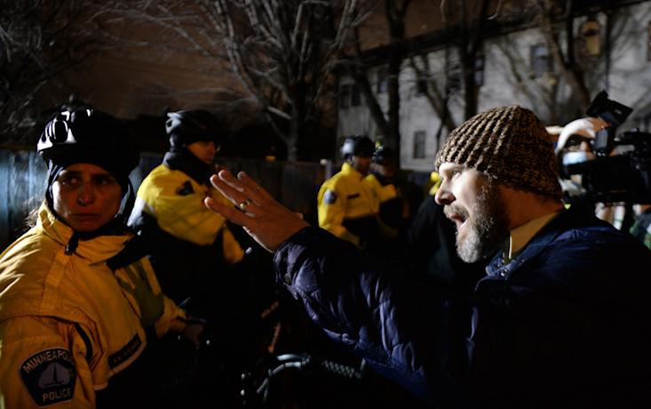 Pastor Tanden Brekke, right, pleads with officers to deescalate the situation as demonstrators besiege the Minneapolis Police Department Fourth Precinct building on Wednesday. Protesters have been camping outside the building since the fatal police shooting of Jamar Clark. (John Autey/Pioneer Press via AP)