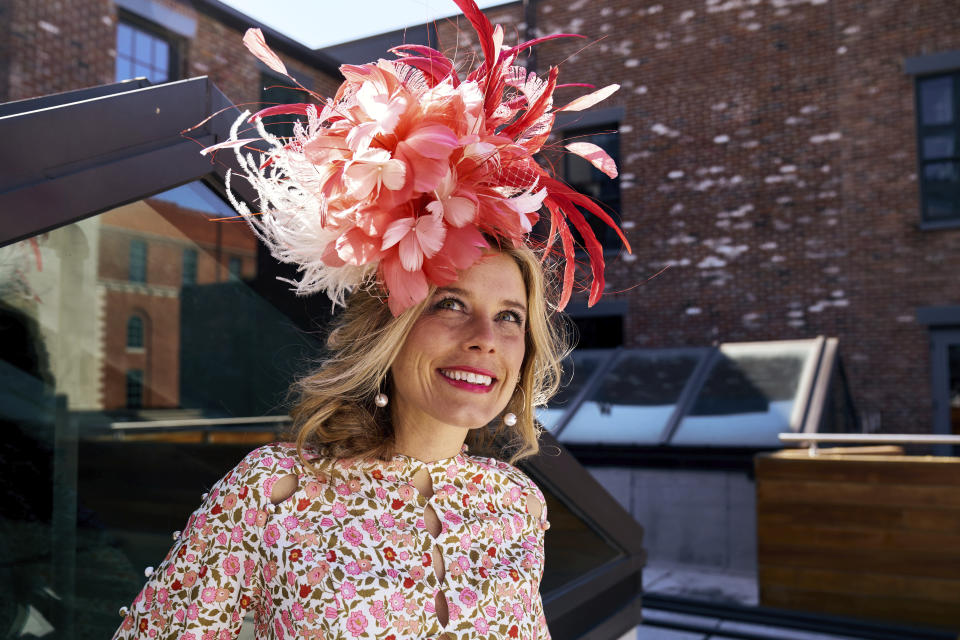 "FILE - In this undated photo provided by Jessa Mayhew in April 2020, hat maker Kenzie Kapp models one of her fascinator designs for the Kentucky Derby in Louisville, Ky. The Kentucky Derby is back on the first Saturday in May 2021, slowly bringing with it the sights, sounds and rituals familiar to Louisville. And local officials and business owners are hopeful it translates into better cash flow after the coronavirus pandemic upended the Derby's schedule the previous year. ""It definitely smells like Derby,"" said business owner and Louisville native Kapp, who's relishing a boost in demand making masks to match her hats and fascinators. (Jessa Mayhew via AP)"