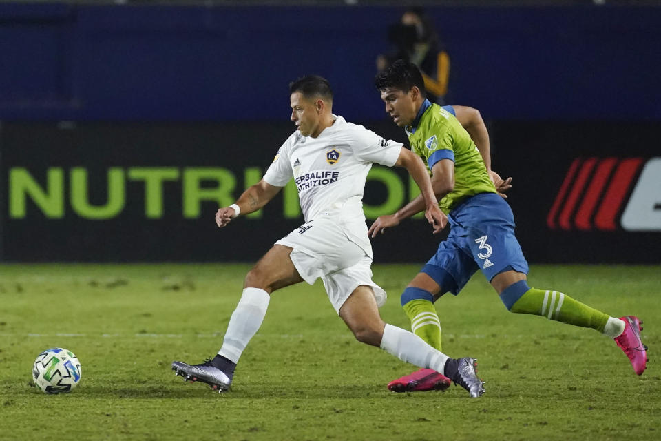 LA Galaxy forward Javier Hernandez, left, takes a shot for a goal ahead of Seattle Sounders defender Xavier Arreaga during the second half of an MLS soccer match Wednesday, Nov. 4, 2020, in Carson, Calif. (AP Photo/Ashley Landis)