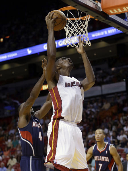 Miami Heat's Chris Bosh, right, goes to the basket as Atlanta Hawks' Paul Millsap, left, defends in the first quarter of an NBA preseason basketball game, Monday, Oct. 7, 2013, in Miami. (AP Photo/Alan Diaz)