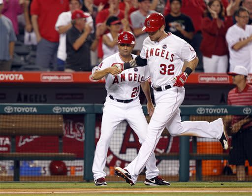 Los Angeles Angels third base coach Dino Ebel congratulates Josh Hamilton (32) for hitting a two-run home run against the St. Louis Cardinals in the ninth inning during a baseball game Thursday, July 4, 2013, in Anaheim, Calif. The Angels won the game 6-5. (AP Photo/Alex Gallardo)