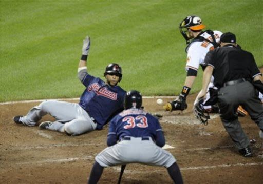 Cleveland Indians' Carlos Santana, left, slides home to score on a single by Michael Brantley against Baltimore Orioles catcher Matt Wieters, right, during the sixth inning of a baseball game, Monday, June 24, 2013, in Baltimore. Cleveland Indians' Nick Swisher (33) and home plate umpire Scott Barry watch. The Indians won 5-2. (AP Photo/Nick Wass)