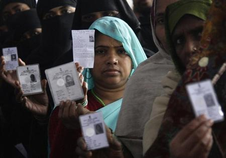 Voters display their voter identity cards as they wait for their turn to cast their ballot at a polling station at Basti, during the state assembly election in the northern Indian state of Uttar Pradesh February 8, 2012.