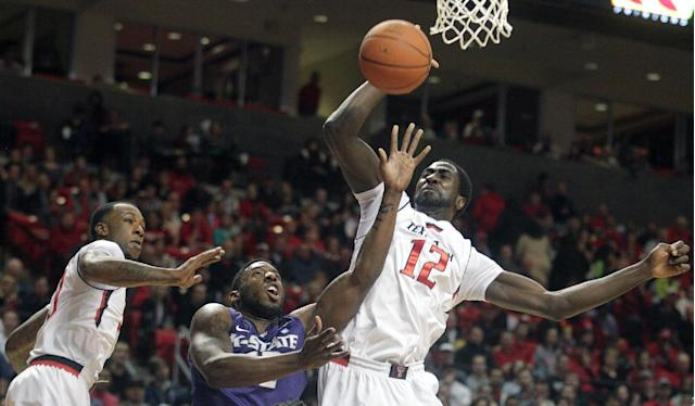 Kansas State's Omari Lawrence (12) is defended by Texas Tech's Jamal Williams, Jr.(23) and Kader Tapsoba (12) during an NCAA college basketball game in Lubbock, Texas, Tuesday, Feb, 25, 2014. (AP Photo/Lubbock Avalanche-Journal, Stephen Spillman)