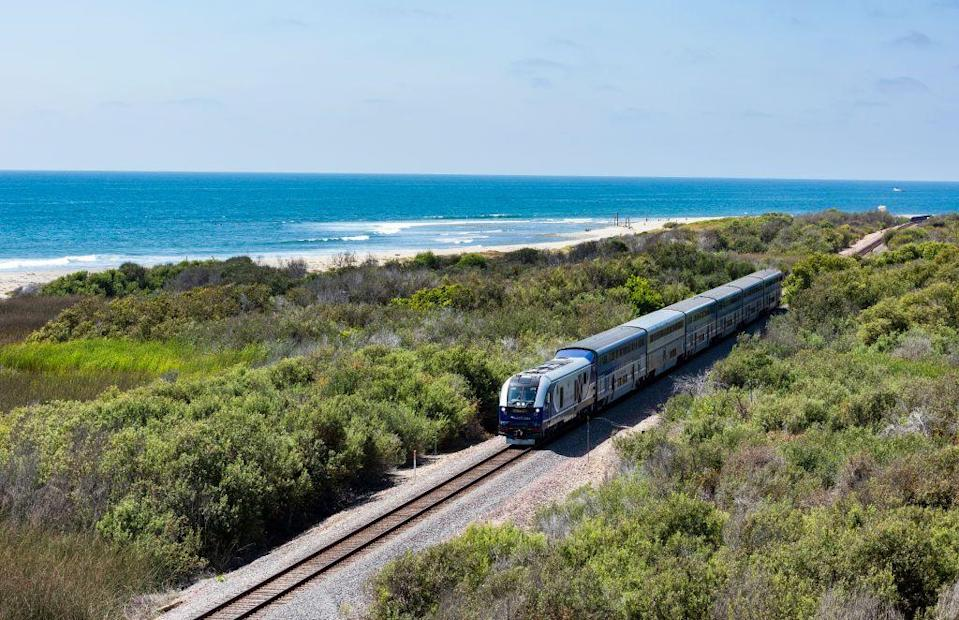 """<p>Tourists and locals alike should check out Southern California's <a href=""""https://www.pacificsurfliner.com/"""" rel=""""nofollow noopener"""" target=""""_blank"""" data-ylk=""""slk:Pacific Surfliner"""" class=""""link rapid-noclick-resp"""">Pacific Surfliner </a>route. Operated by Amtrak, the coastal trek stretches from San Louis Obispo to San Diego, with stops in major cities like Santa Barbara, Los Angeles, and Irvine. An eight-plus journey from beginning to end, the route offers unreal views of the Pacific Ocean and makes a host of attractions accessible along the way (think: beaches, wineries, and major stadiums). </p>"""