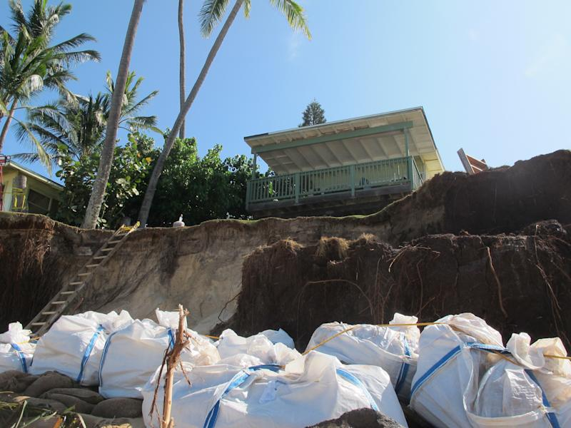 Sandbags are piled up in front of a house damaged by severe beach erosion in the Rocky Point neighborhood of Oahu's North Shore in Haleiwa, Hawaii on Tuesday, Dec. 31, 2013. Some property owners want to be able to install a seawall or something similar to protect their property, but scientists say doing so could lead the sand on the nearby coastline _ including Sunset Beach, home to some of the world's top surfing contests _ to disappear. (AP Photo/Audrey McAvoy)