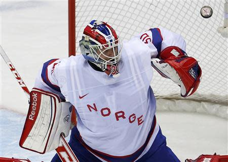 Norway's goalie Lars Haugen makes a save on Austria during the first period of their men's preliminary round ice hockey game at the Sochi 2014 Winter Olympic Games, February 16, 2014. REUTERS/Grigory Dukor