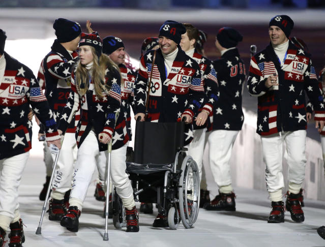 Freeskier Heidi Kloser of the United States, left, walks on crutches after she injured her right leg during a training run before moguls qualifying as she arrives for the opening ceremony of the 2014 Winter Olympics in Sochi, Russia, Friday, Feb. 7, 2014. (AP Photo/Mark Humphrey)