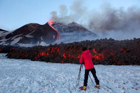FILE PHOTO: A tourist stands in front of Italy's Mount Etna, Europe's tallest and most active volcano, as it spews lava during an eruption on the southern island of Sicily