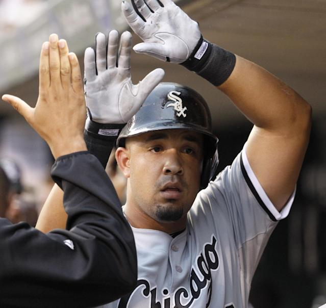 Chicago White Sox's Jose Abreu is congratulated in the dugout after his three-run home run off Minnesota Twins starting pitcher Kevin Correia during the first inning of a baseball game in Minneapolis, Friday, July 25, 2014. (AP Photo/Ann Heisenfelt)