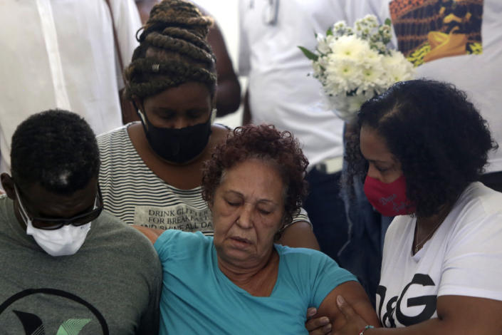 Supported by relatives, Angela Romeu, center, the grandmother of Kathlen Romeu, a young pregnant woman killed by a stray bullet, attends her granddaughter's funeral in Rio de Janeiro, Brazil, Wednesday, June 9, 2021. Rio's police have said the 20-something interior designer was hit by a single shot in her torso during a shootout with criminals. Officers brought her to a nearby hospital, but neither she nor her baby survived. (AP Photo/Bruna Prado)