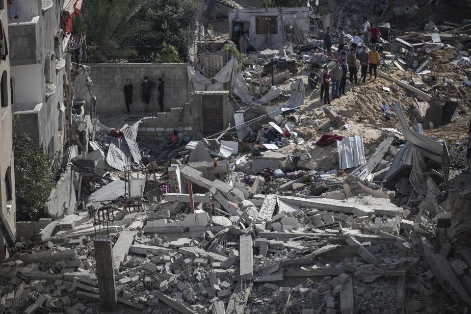 Palestinians inspect the rubble of their destroyed homes after being targeted by Israeli airstrikes in town of Beit Lahiya, northern Gaza Strip, Thursday, May 13, 2021. Gaza braced for more Israeli airstrikes and communal violence raged across Israel after weeks of protests and violence in Jerusalem. (AP Photo/Khalil Hamra)