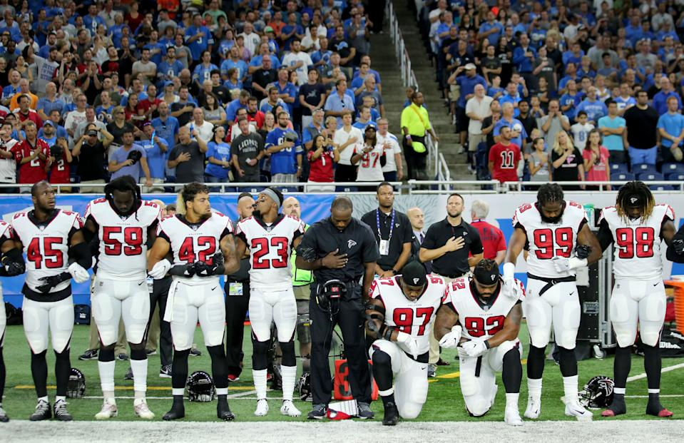 Members of the Atlanta Falcons football team Grady Jarrett and Dontari Poe take a knee during the playing of the national anthem prior to the start of the game against the Detroit Lions at Ford Field on September 24, 2017 in Detroit, Michigan. (Photo by Leon Halip/Getty Images)