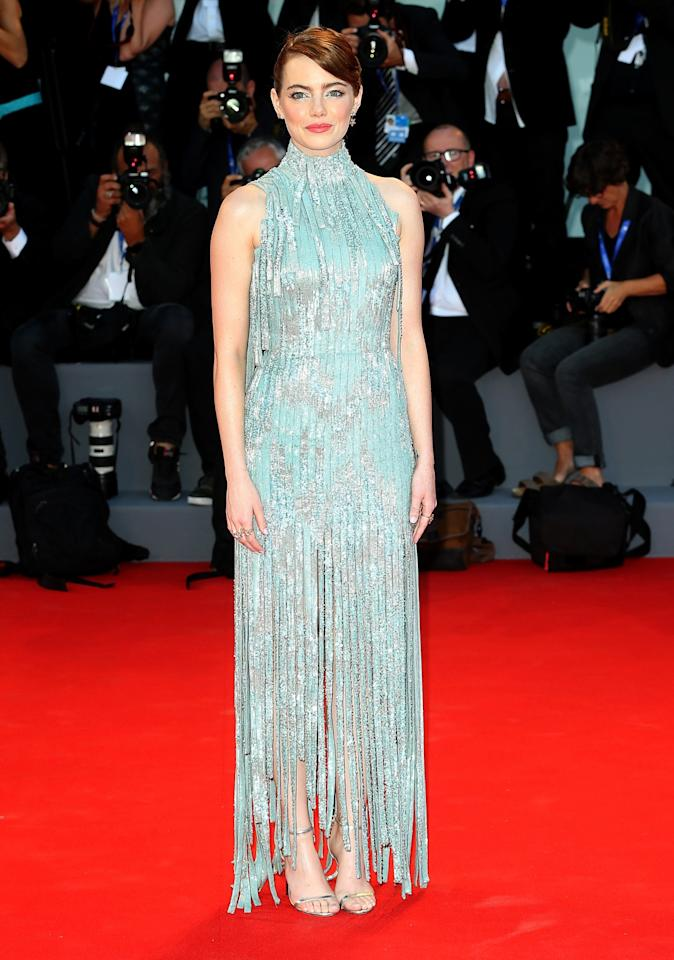 <p>Emma ensured all eyes were on her at Venice Film Festival in this fringed Versace dress. The look was finished with a sleek updo and strappy Jimmy Choos. [Photo: Getty] </p>