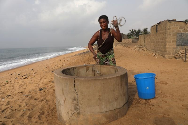 Massi Natou, 46, collects water from a well on a coastline that is threatened by sea storms and coastal erosion in Afidegnigban