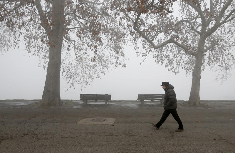 A man walks on the banks of Danube river in Belgrade, Serbia, Wednesday, Jan. 15, 2020.  Serbia's government on Wednesday called an emergency meeting, as many cities throughout the Balkans have been hit by dangerous levels of air pollution in recent days, prompting residents' anger and government warnings to stay indoors and avoid physical activity.(AP Photo/Darko Vojinovic)