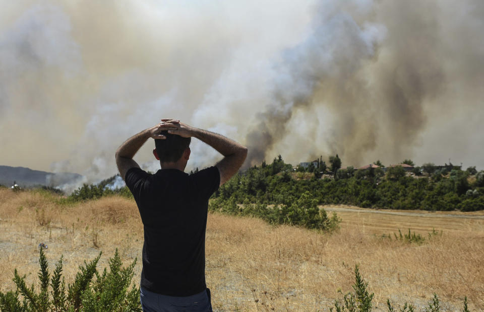A man watches wildfires in Kacarlar village near the Mediterranean coastal town of Manavgat, Antalya, Turkey, Saturday, July 31, 2021. The death toll from wildfires raging in Turkey's Mediterranean towns rose to six Saturday after two forest workers were killed, the country's health minister said. Fires across Turkey since Wednesday burned down forests, encroaching on villages and tourist destinations and forcing people to evacuate. (AP Photo)