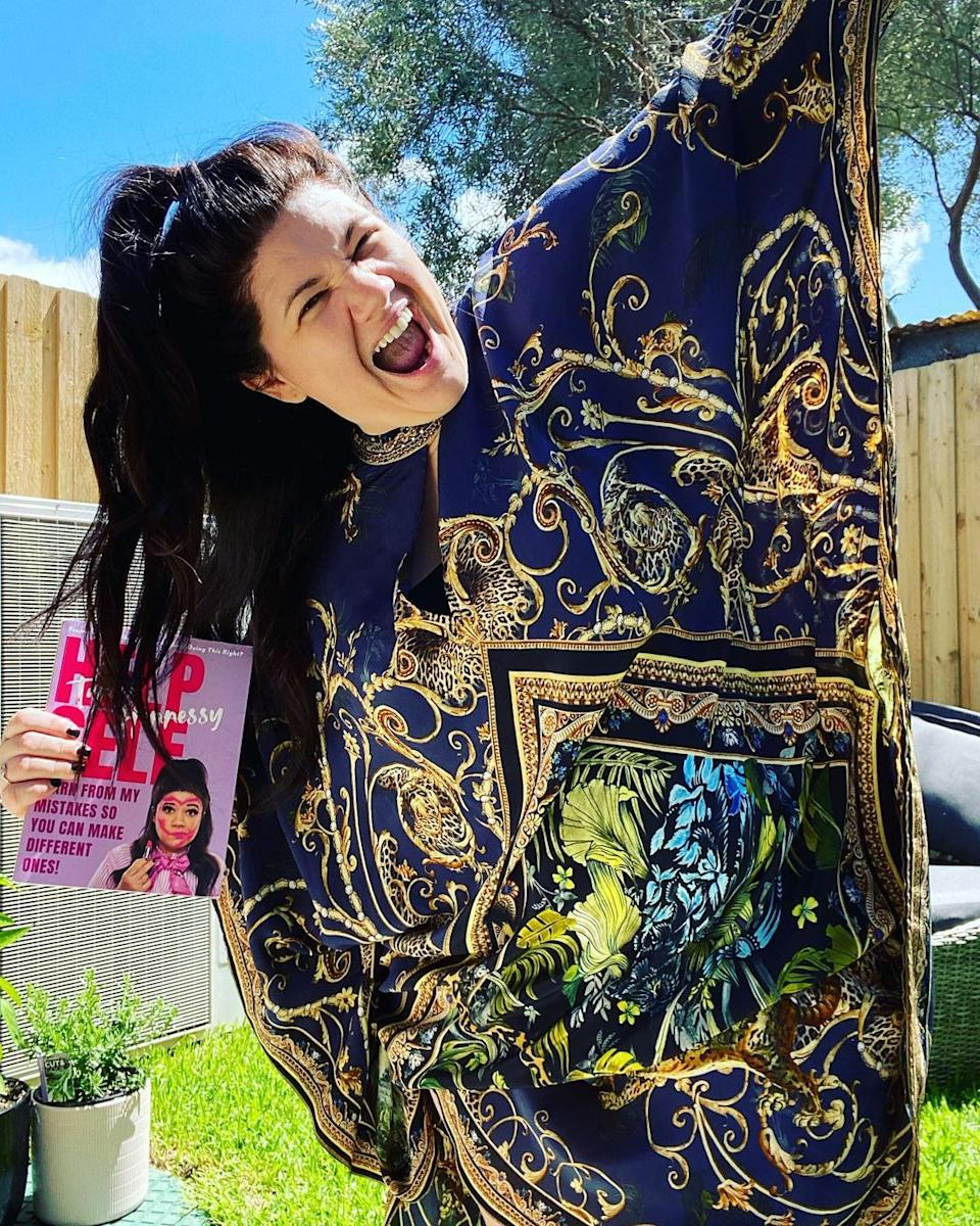 Tanya Hennessy wearing a blue and gold kaftan while holding a copy of her new book, Help Self