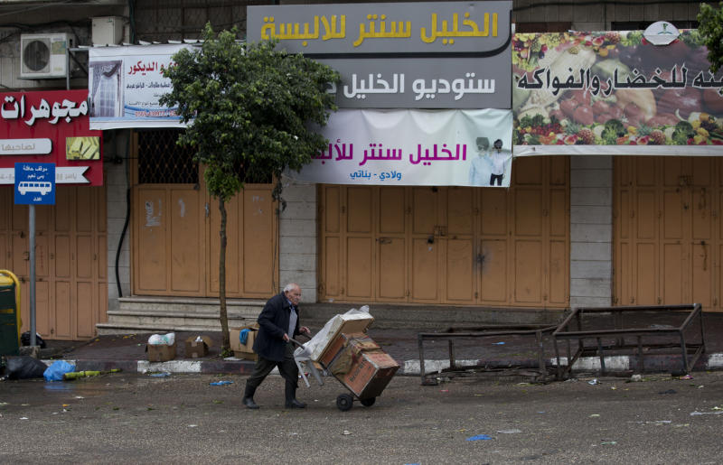 A Palestinian man walks in front of a closed shop during a general strike in the West Bank city of Hebron, Monday, Dec. 9, 2019. Palestinian residents held a general strike to protest an Israeli plan to build a new Jewish neighborhood in the heart of the West Bank's largest city.  (AP Photo/Majdi Mohammed)