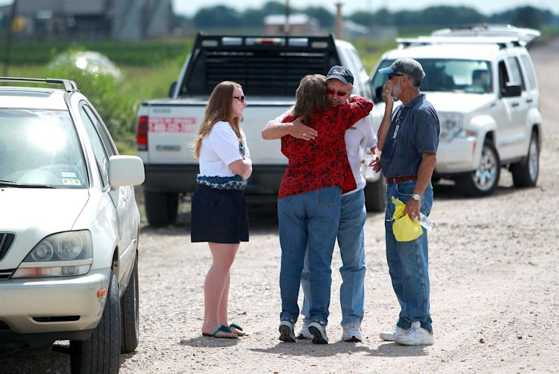 People greet each other near the site where a glider crashed killing three people including a 3-year-old boy Monday, June 18, 2012, in Wallis, Texas. Authorities are trying to determine what led to the crash that happened at about 5 p.m. Sunday near the glider facility at Texas 36 and Cougar Drive. Deputies said Fred Blair, 68, of Wallis, and Matilda Blair, 32, and 3-year-old Andrew Blair of Houston died instantly in the crash. (AP Photo/Houston Chronicle ,Johnny Hanson)