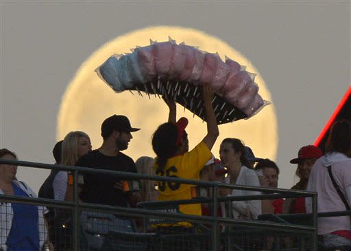 A cotton candy vendor, center, walks in from of the moon during the Los Angeles Angels' baseball game against the Pittsburgh Pirates, Saturday, June 22, 2013, in Anaheim, Calif. (AP Photo/Mark J. Terrill)
