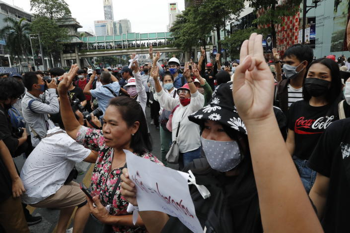 Pro-democracy protesters gather, flashing three-fingered salutes at a main shopping district in Bangkok, Thailand, Sunday, Oct. 25, 2020. Thailand's government and the country's pro-democracy movement appeared no closer to resolving their differences Saturday, as the protesters' deadline for Prime Minister Prayuth Chan-ocha to step down came and went with no new action from either side, and no backing down.(AP Photo/Gemunu Amarasinghe )