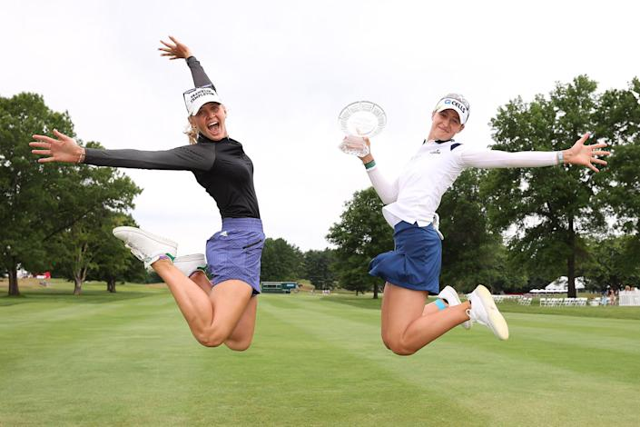 Nelly Korda and her sister Jessica Korda jump on a golf course