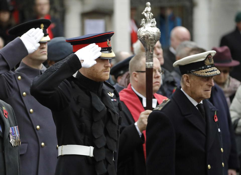 FILE - In this file photo dated Thursday, Nov. 10, 2016, Britain's Prince Harry salutes as he and Prince Philip attend the official opening of the annual Field of Remembrance at Westminster Abbey in London. The Field of Remembrance pays tribute to all the people who have served in the British armed forces since World War I. Prince Philip who died Friday April 9, 2021, aged 99, lived through a tumultuous century of war and upheavals, but he helped forge a period of stability for the British monarchy under his wife, Queen Elizabeth II. The decades brought family troubles, including the self-exile of grandson Prince Harry and his wife Meghan amid allegations of racism.(AP Photo/Matt Dunham, FILE)