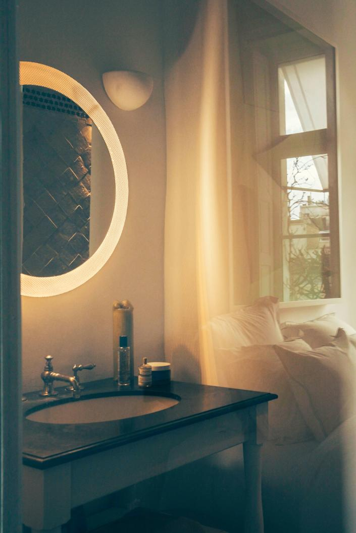 """<div class=""""caption""""> A round backlit mirror, sourced at a local gallery, makes a statement in the bathroom, which floods with sunlight from the south-facing windows. </div>"""