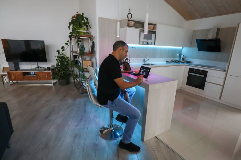 Echevarria, founder of the building company specialised in all-wood, low-emission homes 100x100 Madera, checks the air quality in his house, in Guadalix de la Sierra