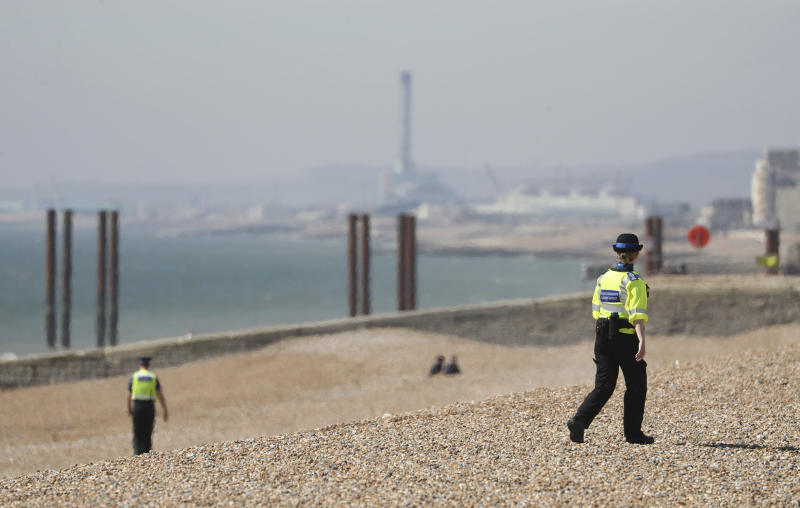 Police community support officers patrol Brighton beach, south England, Sunday April 5, 2020,as the UK continues in lockdown to help curb the spread of the coronavirus. The new coronavirus causes mild or moderate symptoms for most people, but for some, especially older adults and people with existing health problems, it can cause more severe illness or death. (Andrew Matthews/PA via AP)