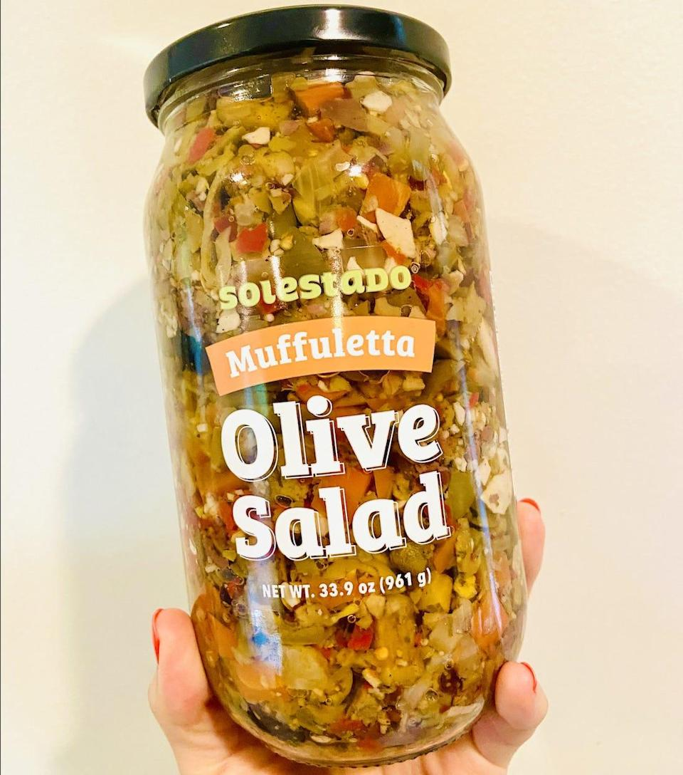 A hand holding a jar of olive salad, which is brown and red