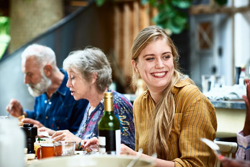 Cheerful woman in her 30s with long blond hair sitting with friends, socialising, eating with friends at home