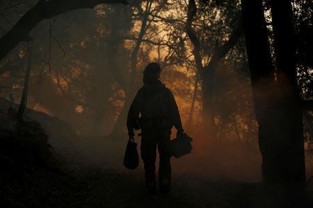 A firefighter brings supplies to crewmates, while working to control a wildfire in Sonoma, California, U.S., October 14, 2017. REUTERS/Jim Urquhart