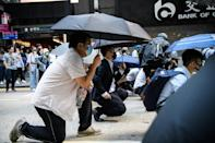 Office workers join the front lines after police fired tear gas during a flash mob protest in the Central district of Hong Kong
