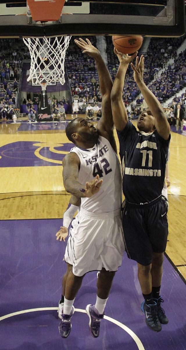 George Washington's Kethan Savage (11) shoots under pressure from Kansas State's Thomas Gipson (42) during the first half of an NCAA college basketball game Tuesday, Dec. 31, 2013, in Manhattan, Kan. (AP Photo/Charlie Riedel)