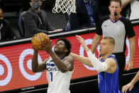 Minnesota Timberwolves forward Anthony Edwards, left, shoots in front of Dallas Mavericks center Kristaps Porzingis, right, in the first quarter during an NBA basketball game, Sunday, May 16, 2021, in Minneapolis. (AP Photo/Andy Clayton-King)