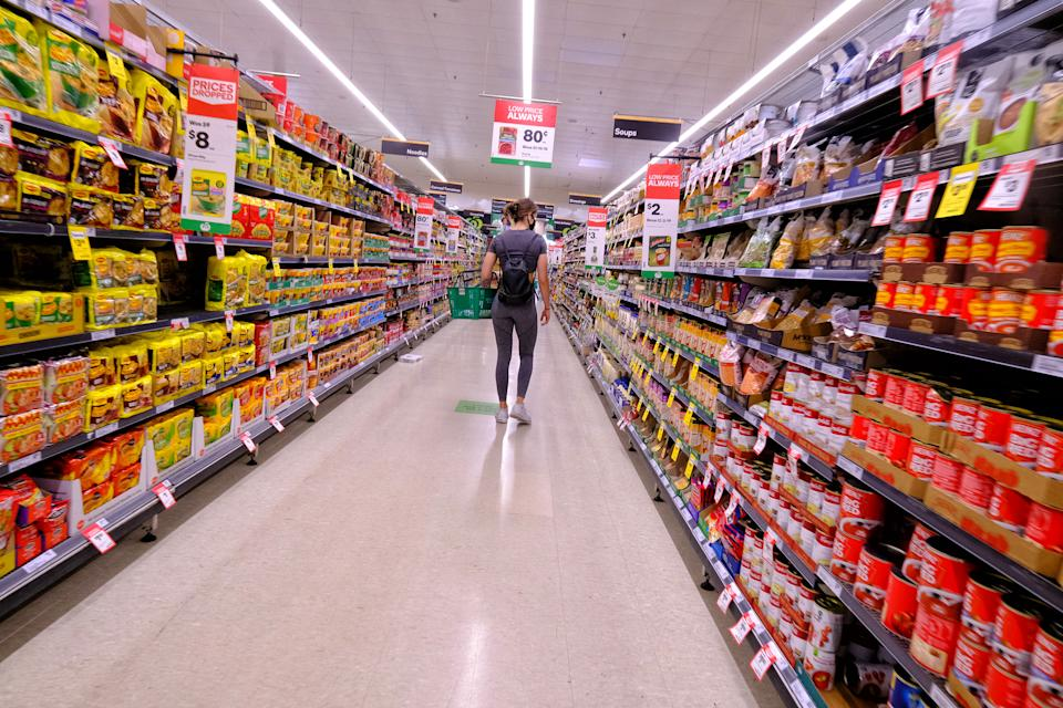 Pictured is a person walking down an aisle at a Woolworths supermarket.