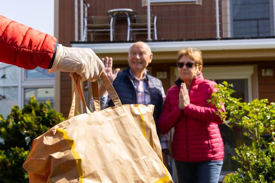 shallow focus on hand with gloves bringing paper bag with food for thankful senior couple in their garden staying at home during coronavirus pandemic crisis