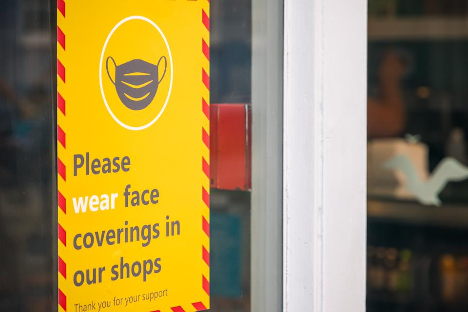 Suffolk, UK - 1 August, 2020 - Face coverings warning sign displayed outside a shop in Southwold town