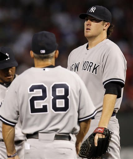 New York Yankees manager Joe Girardi (28) walks to the mound to pull starting pitcher Phil Hughes, right, in the third inning a baseball game against the Texas Rangers, Wednesday, April 25, 2012, in Arlington, Texas. (AP Photo/Tony Gutierrez)