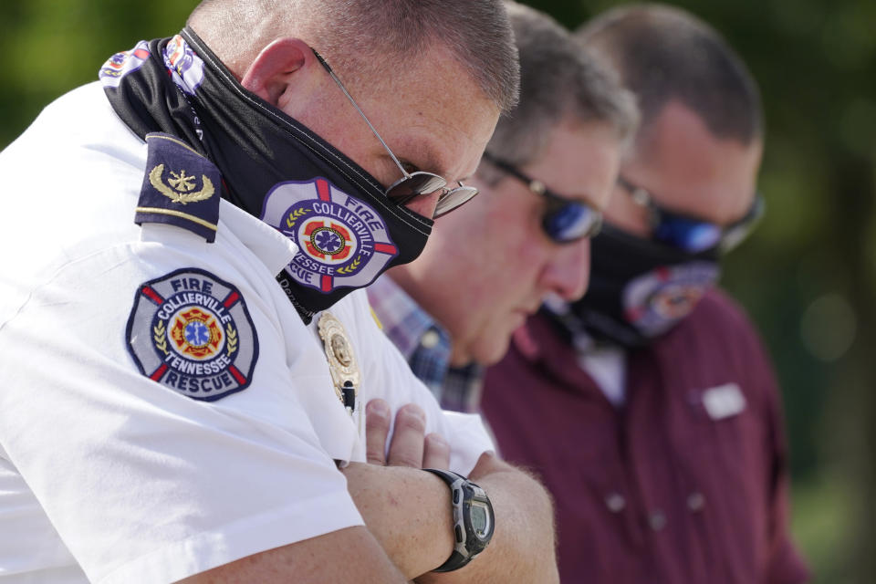 Tommy Kelley, left, of the Collierville Fire Department, prays during a vigil at the Collierville Town Hall Friday, Sept. 24, 2021, in Collierville, Tenn. The vigil is for the person killed and those injured when a gunman attacked people in a Kroger grocery store Thursday before he was found dead of an apparent self-inflicted gunshot wound. (AP Photo/Mark Humphrey)