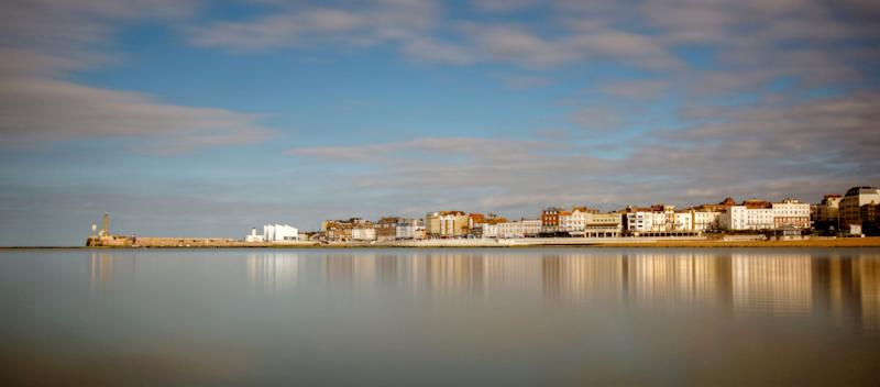 Seaside town beach water reflections of Margate harbour.