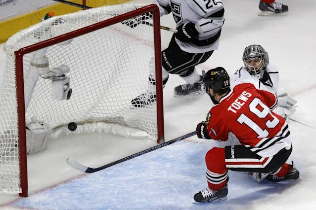 Chicago Blackhawks center Jonathan Toews (19) scores a goal against Los Angeles Kings goalie Jonathan Quick (32) during the first period in Game 7 of the Western Conference finals in the NHL hockey Stanley Cup playoffs Sunday, June 1, 2014, in Chicago. (AP Photo/Charles Rex Arbogast)