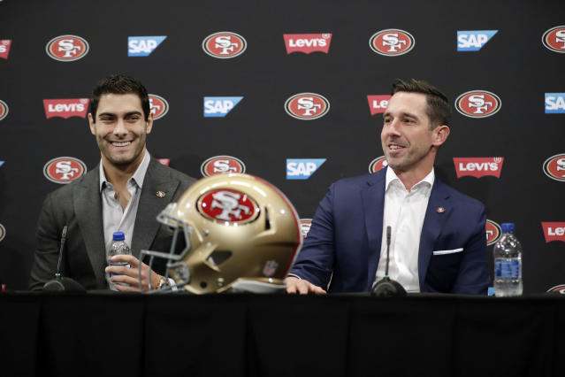 San Francisco 49ers quarterback Jimmy Garoppolo, left, smiles next to head coach Kyle Shanahan during an NFL football press conference Friday, Feb. 9, 2018, in Santa Clara, Calif. Garoppolo has signed a five-year contract with the 49ers worth a record-breaking $137.5 million. (AP Photo/Marcio Jose Sanchez)