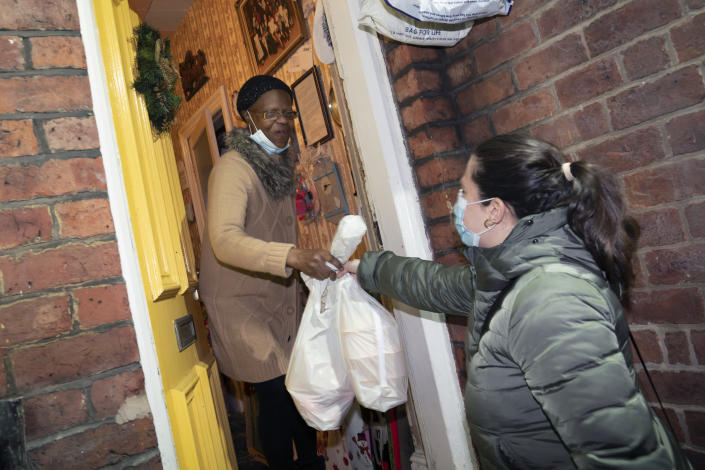 Volunteer Maria Martinez, right, hands bags of West Indian meals to Bridgette Toussaint, prepared by members of the Preston Windrush Covid Response team, in Preston, England, Friday Feb. 19, 2021. Once a week chief coordinator Glenda Andrew and her team distribute meals to people in Preston and surrounding communities in northwestern England that have recorded some of the U.K.'s highest coronavirus infection rates. The meal program grew out of Andrew's work with Preston Windrush Generation & Descendants, a group organized to fight for the rights of early immigrants from the Caribbean and other former British colonies who found themselves threatened with deportation in recent years. (AP Photo/Jon Super)