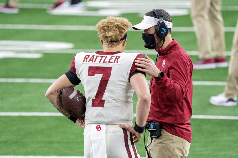 Oklahoma head coach Lincoln Riley talks with quarterback Spencer Rattler (7) before the Big 12 Conference championship NCAA college football game against Iowa State, Saturday, Dec. 19, 2020, in Arlington, Texas. (AP Photo/Jeffrey McWhorter)