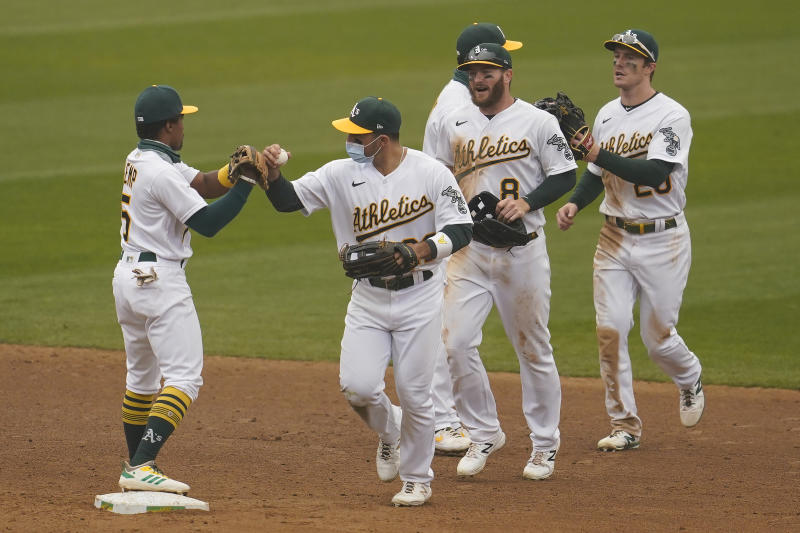 Oakland Athletics' Tony Kemp celebrates with Ramon Laureano, Robbie Grossman, Marcus Semien (top obscured) and Mark Canha, from left, after the Athletics defeated the Houston Astros in a baseball game in Oakland, Calif., Thursday, Sept. 10, 2020. (AP Photo/Jeff Chiu)