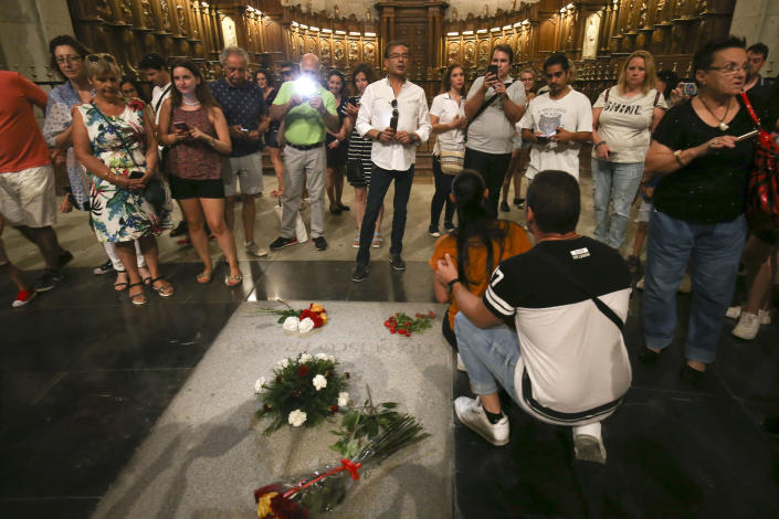 People stand around the tomb of former Spanish dictator Francisco Franco inside the basilica at the the Valley of the Fallen monument near El Escorial, outside Madrid on Friday, Aug. 24, 2018. Spain's center-left government has approved legal amendments that it says will ensure the remains of former dictator Gen. Francisco Franco can soon be dug up and removed from a controversial mausoleum. (AP Photo/Andrea Comas)